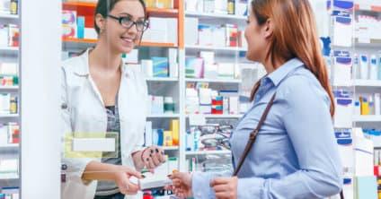 pharmacist handing medicine to customer