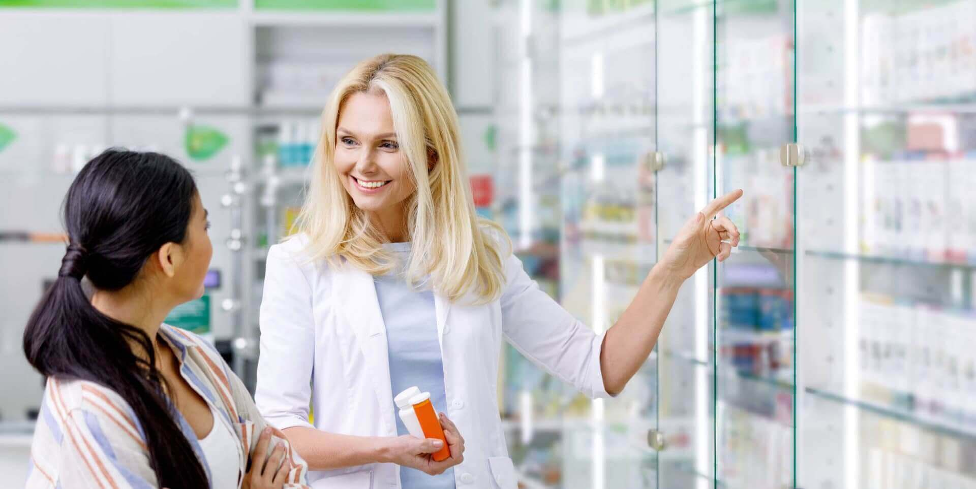 pharmacist holding medicines helping customer
