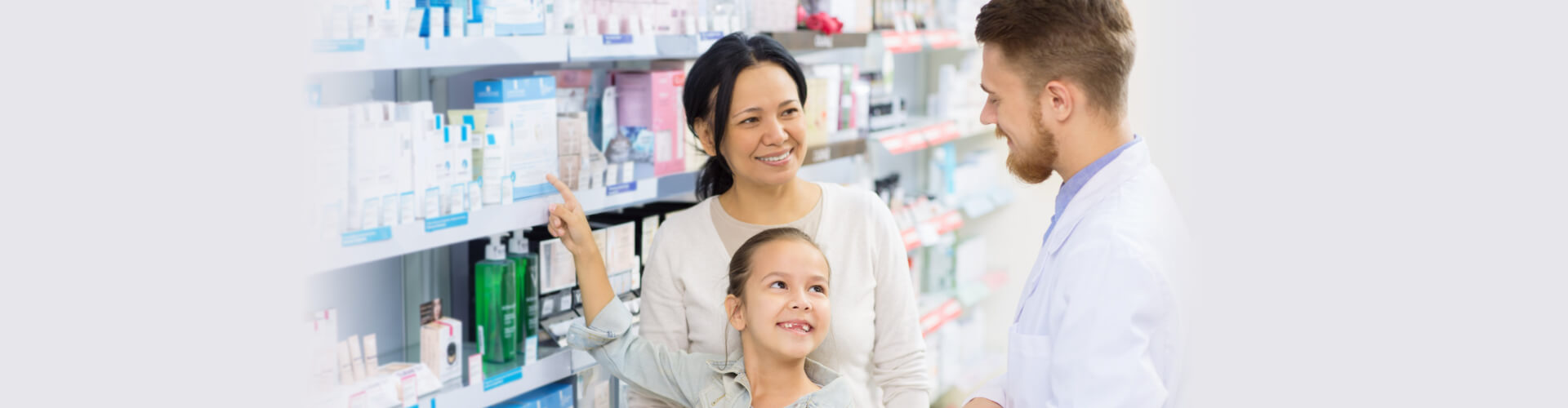 girl pointing to medicine beside mother and pharmacist